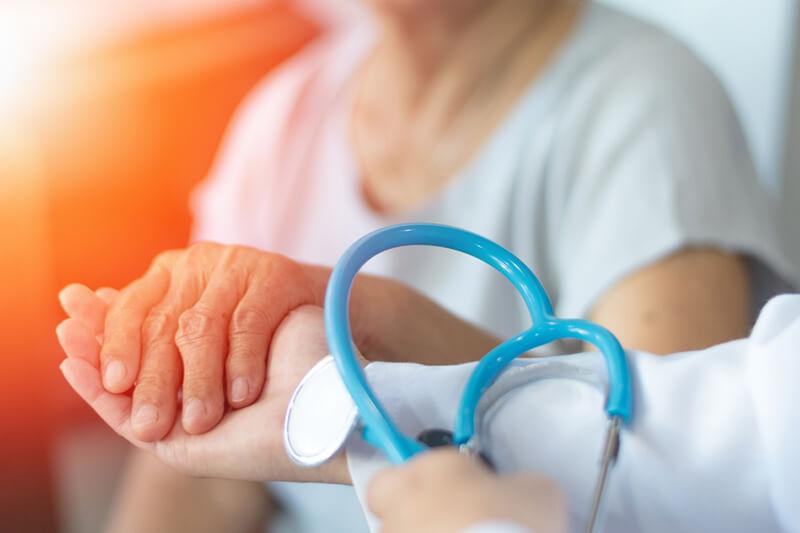 진료 중 환자와 손잡는 의사